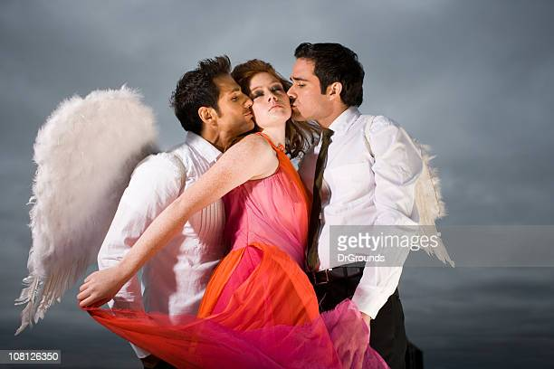 two men wearing angel wings kissing young woman - male angel stock photos and pictures