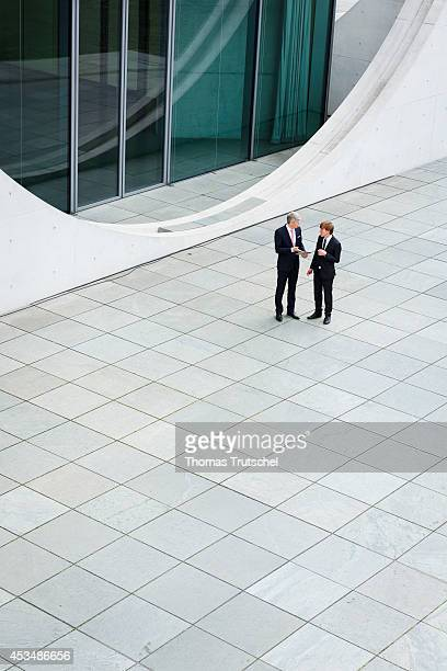 Two men wearing business business suits talk to each other on August 07 2014 in Berlin Germany