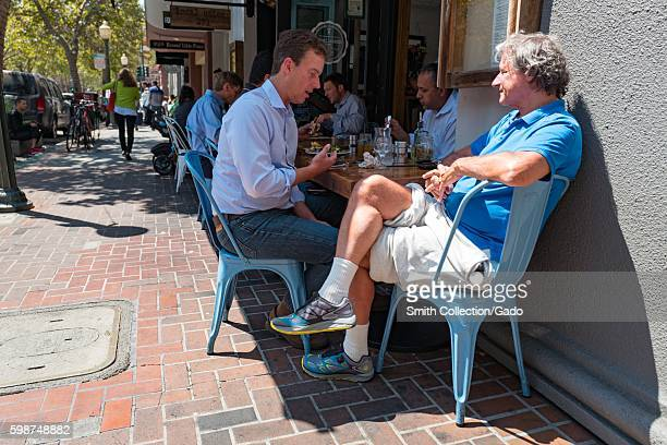 Two men wearing business casual attire eat lunch and converse at Local Union 271, a farm to table restaurant on University Avenue in the Silicon...