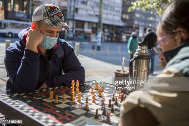 Two men wearing face masks drink mate and play chess on May 07, 2020 in Montevideo, Uruguay. President Lacalle Pou called for a reopening of certain...