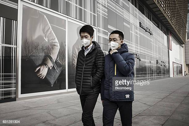 Two men wearing face masks walk past a an Ermenegildo Zegna Ltd store in Beijing China on Friday Jan 6 2017 Toxic haze that settled over much of...