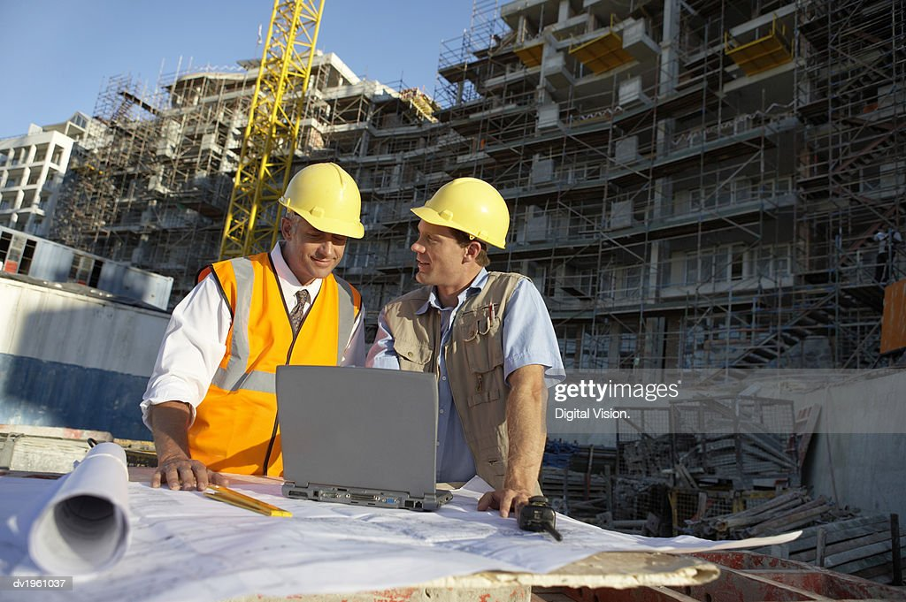 Two Men Wearing Hard Hats Looking at a Laptop Computer on a Building Site : Stock Photo