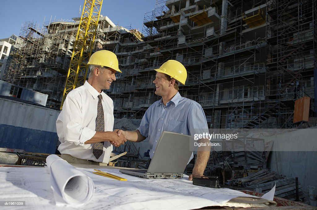 Two Men Wearing Hard Hats Shaking Hands, on a Building Site : Stock Photo