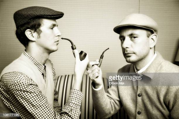 Two Men Wearing Newsboy Caps and Smoking Pipes
