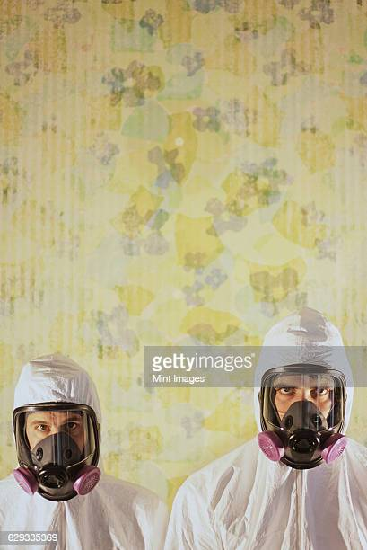 Two men wearing protective hazmat or clean suits in a room, with a background wall decorated with wallpaper.