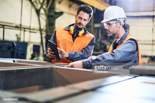 two men wearing protective workwear working with tablet in factory - safe security equipment stock pictures, royalty-free photos & images