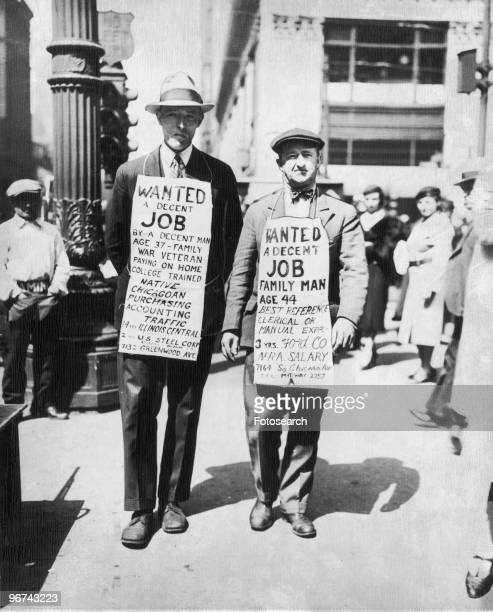 Two men wearing sandwich boards advertising their willingness to find employment - 'Wanted, a decent job' - in Chicago during the Great Depression....
