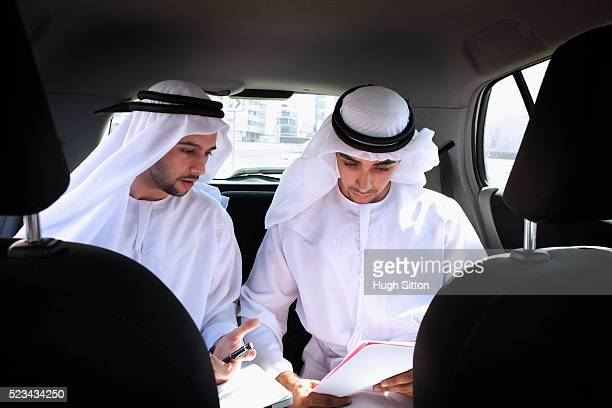 two men wearing traditional clothing doing paperwork on backseat of car - hugh sitton stock-fotos und bilder