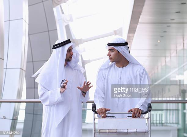 two men wearing traditional clothing pushing luggage trolley at airport and talking - hugh sitton imagens e fotografias de stock