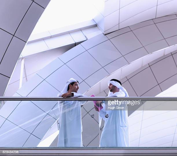 two men wearing traditional clothing talking in front of modern office building - hugh sitton stock pictures, royalty-free photos & images