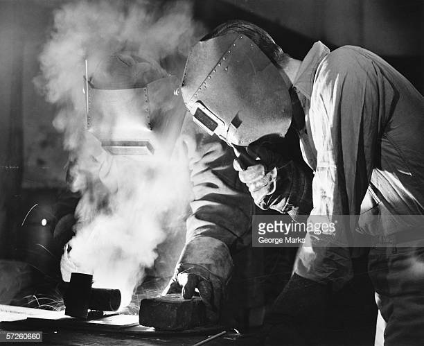 two men welding, holding protective masks, (b&w) - 20th century stock pictures, royalty-free photos & images