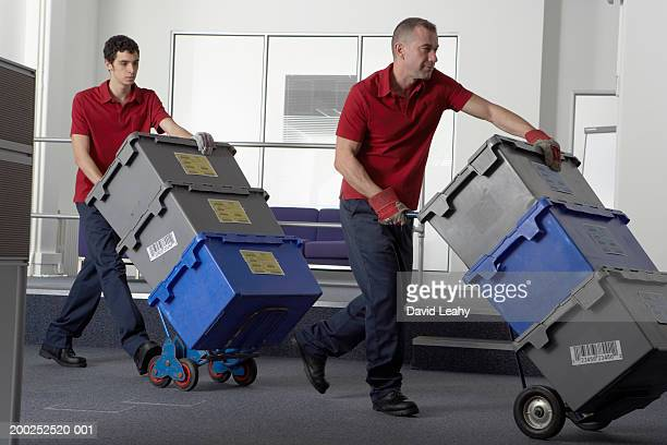 Two men wheeling crates on sack barrows through office area