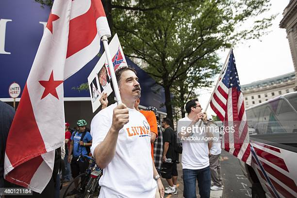 Two men with a District of Columbia flag and an American flag gather in front of the under construction Trump Hotel to protest Donald Trump,...