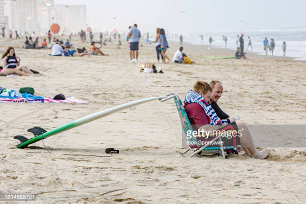 Two men with a surfboard propped up on the back of a chair relax and enjoy the beach on May 22 in Virginia Beach VA This is the first day of the...