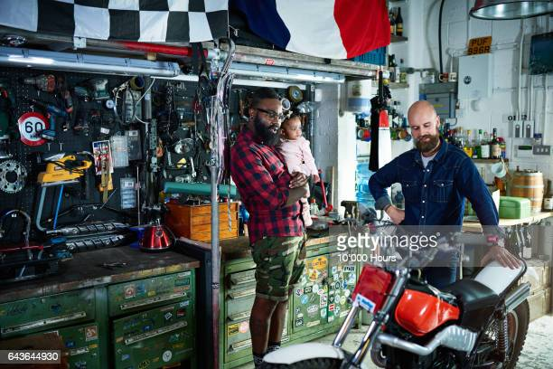 Two men with baby girl in motorcycle workshop.