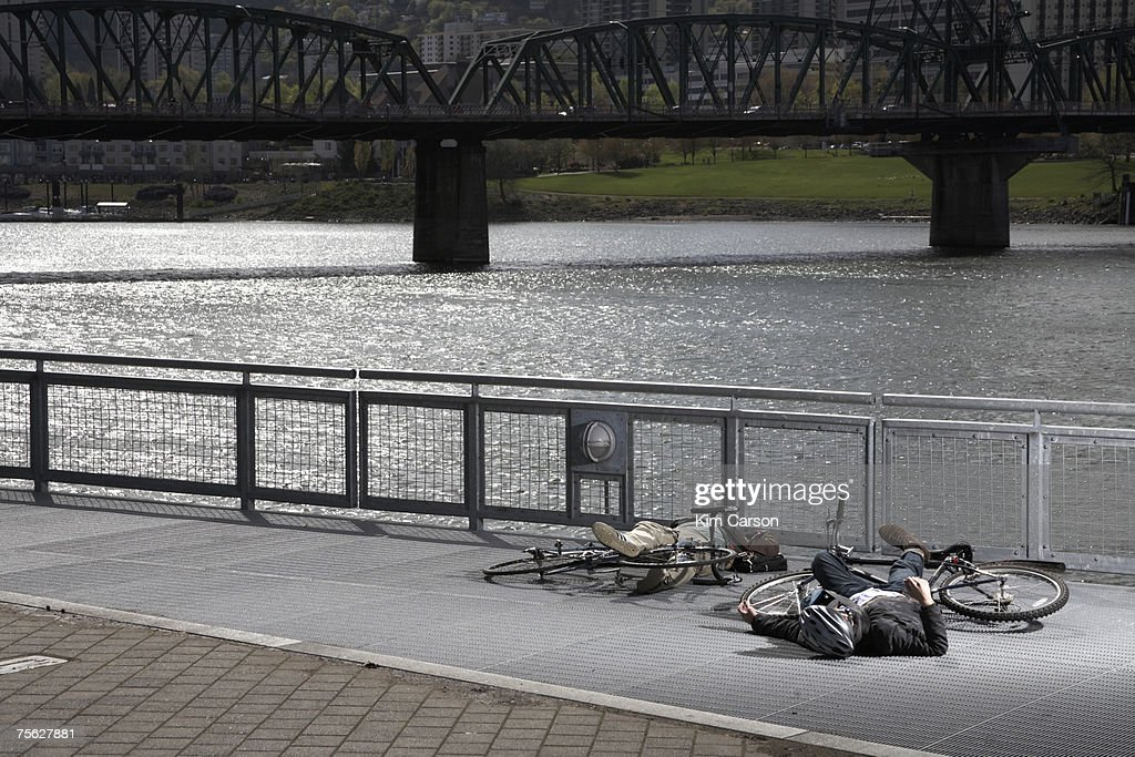 Two men with bicycles lying on pavement by river after collision : ストックフォト