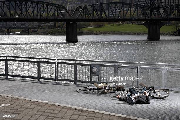 two men with bicycles lying on pavement by river after collision - dead bodies in car accident photos stock pictures, royalty-free photos & images
