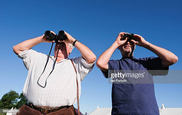 Two men with binoculars watch as a sheepdog drives sheep towards a pen at the British National Sheep Dog Trials on August 6, 2016 in York, England....