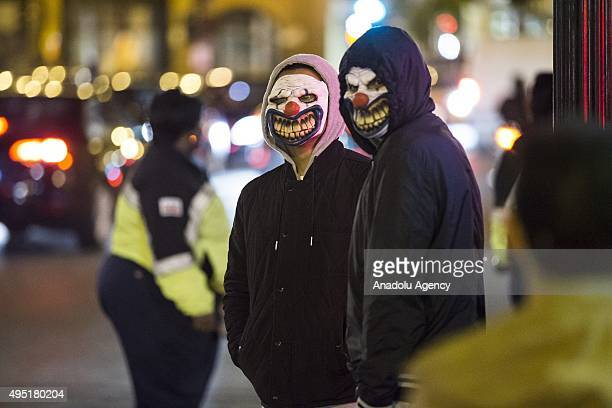 Two men with creepy clown masks for Halloween in the Georgetown neighborhood of Washington USA on October 31 2015