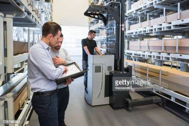 two men with documents and worker with forklift in factory warehouse - loader reading stock pictures, royalty-free photos & images