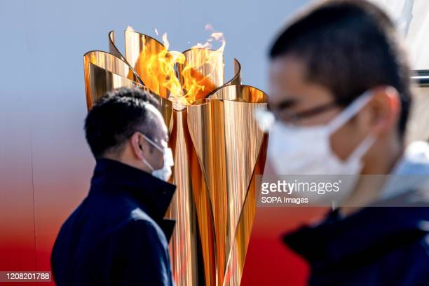 Two men with face mask walk by the Olympic cauldron. 'Flame of Recovery' special exhibition at Aquamarine Park after it was announced that the Tokyo...