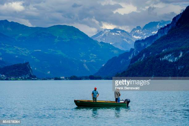 Two men with fishing rods are standing in a rowing boat on Lake Brienz Brienzer See high mountains in the distance