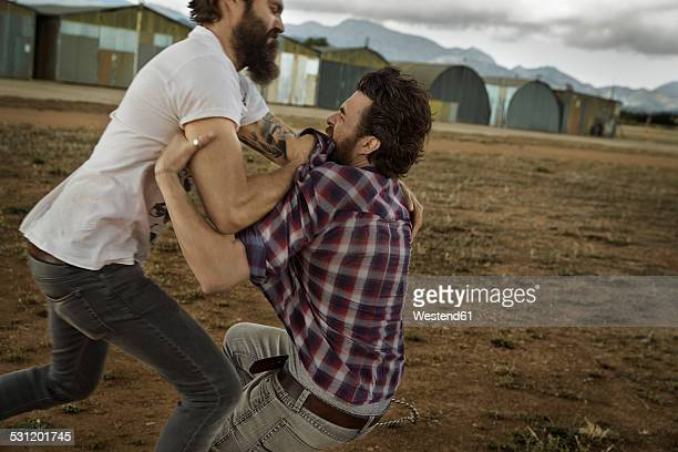 Two men with full beards fighting in abandoned landscape