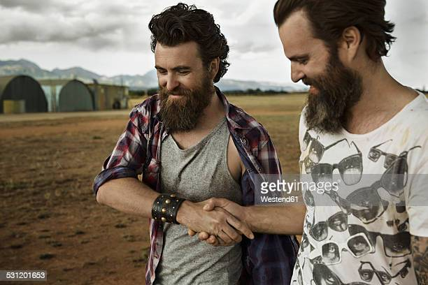 Two men with full beards in abandoned landscape shaking hands