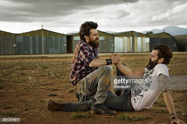 Two men with full beards reconciling after punch-up