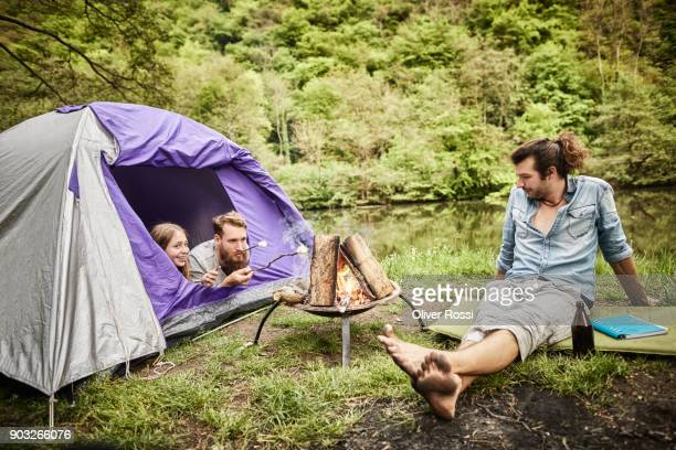 Two men with girl and tent at camp fire