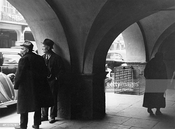 Two men with hat on head chatting under the arcades. Cuneo, 1930s