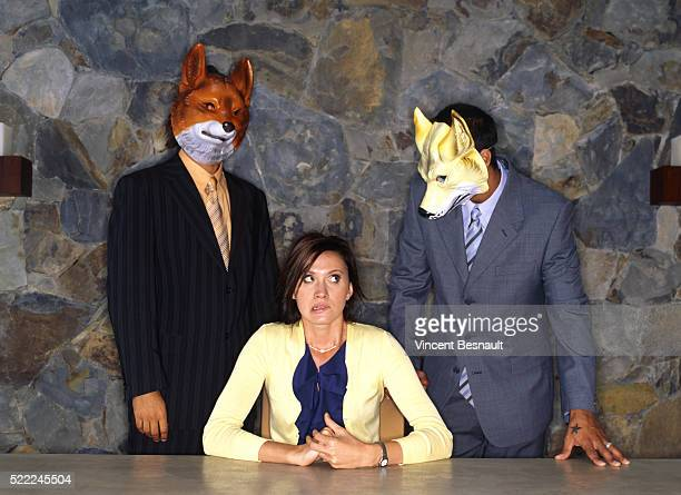 Two Men with Masks Standing Behind Woman Sitting at Table