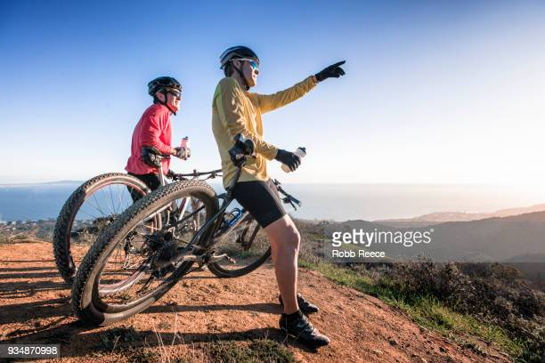 two men with mountain bikes on top of a mountain - robb reece stock pictures, royalty-free photos & images