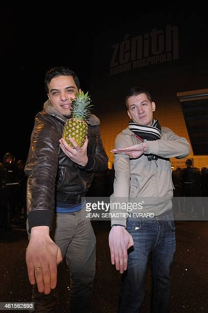 Two men with one of them holding a pineapple perform a quenelle salute in front of a line of French police officers after the performance of French...