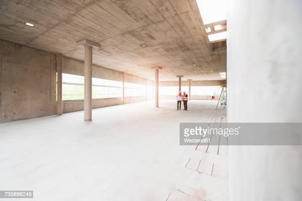 two men with plan wearing safety vests talking in building under construction - baumaterial stock-fotos und bilder