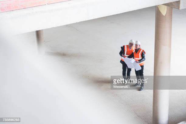 two men with plan wearing safety vests talking in building under construction - kontrolle stock-fotos und bilder