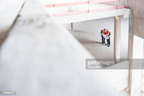 two men with plan wearing safety vests talking in building under construction - struttura edile foto e immagini stock