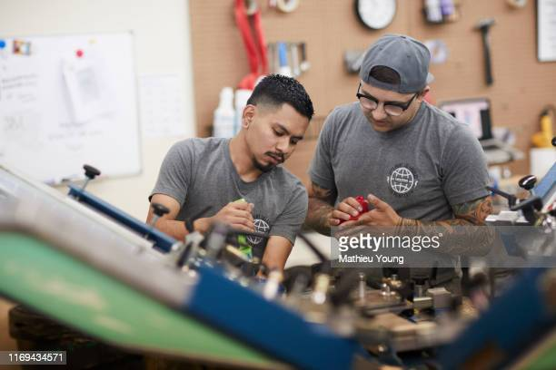 two men with screen printer - graphic print stock pictures, royalty-free photos & images