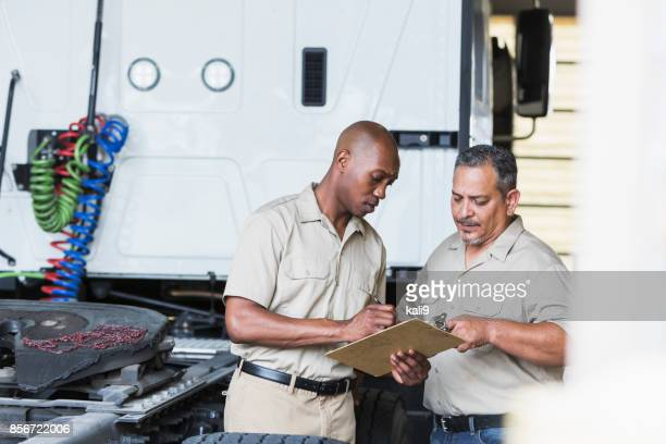 Two men with semi-truck in garage