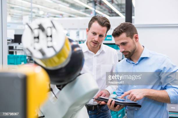 two men with tablet examining assembly robot in factory shop floor - kontrolle stock-fotos und bilder