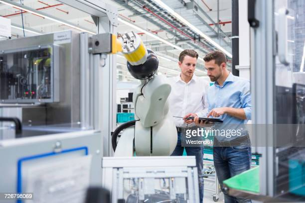 Two men with tablet examining assembly robot in factory shop floor