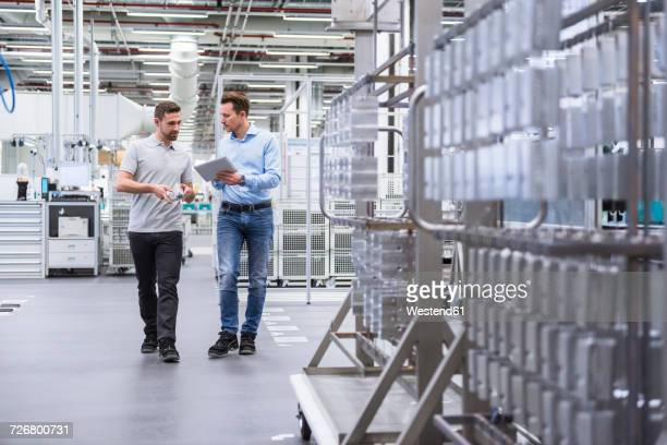 two men with tablet talking about a product in factory shop floor - halle gebäude stock-fotos und bilder