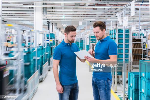 Two men with tablet talking in industrial hall