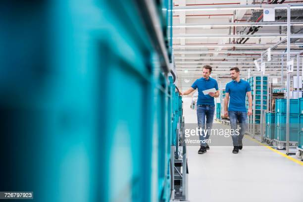 Two men with tablet walking at tugger train in industrial hall
