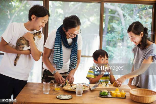 two men, woman and boy gathered around a table, preparing corn on the cob, one man holding cat, smiling. - childhood photos ストックフォトと画像