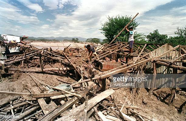 Two men work amid the ruins of destroyed houses 07 November in Choluteca Honduras more than one week after Hurricane Mitch unleashed a murderous...