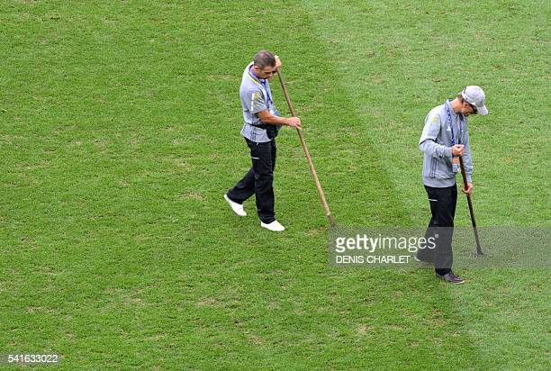 Two men work on the pitch prior to the Euro 2016 group A football match between Switzerland and France at the PierreMauroy stadium in Lille on June...