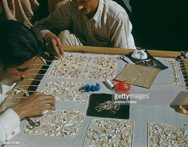Two men working at a rich embroidery in India circa 1965