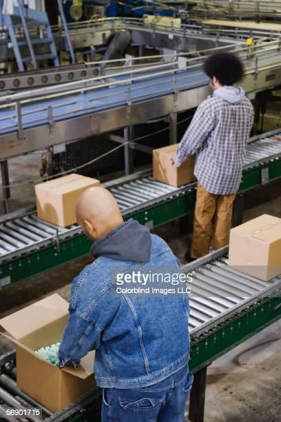 two men working at conveyor belt - unterschicht stereotypen stock-fotos und bilder