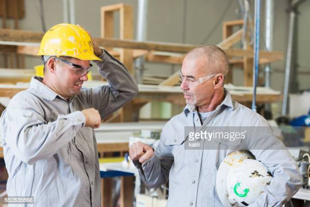 Two men working in a small factory, bumping fists